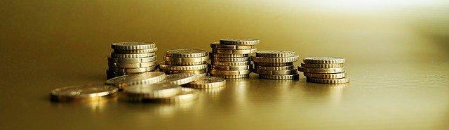 hromádky zlatých mincí na stole