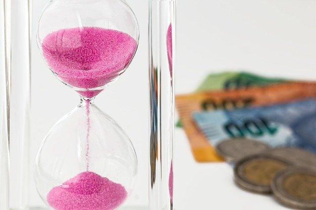 přesýpací hodiny + v pozadí bankovky
