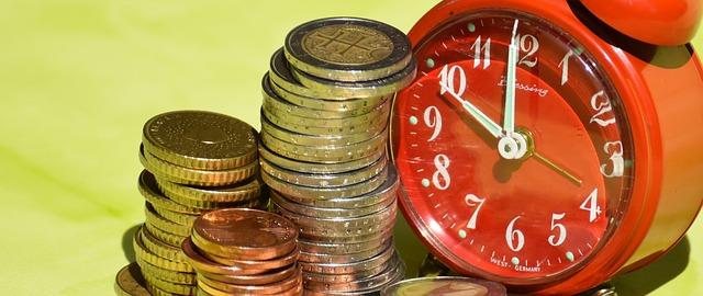tři hromádky mincí + červený budík
